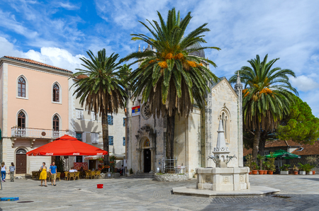 karachi: HERGEG NOVI, MONTENEGRO - SEPTEMBER 25, 2015: Unknown people are relaxing at street cafe on square of Duke Stefan (Bellavista) near Orthodox Church of Archangel Michael and Karachi drinking fountain in popular resort town of Herceg Novi, Montenegro