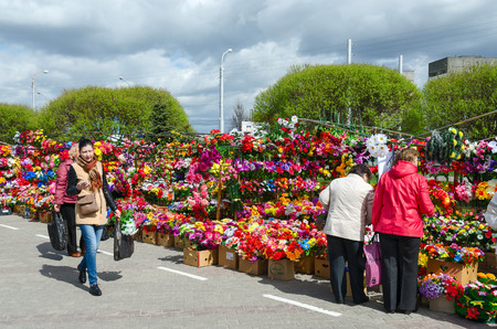 acquirer: GOMEL, BELARUS - APRIL 20, 2016: Unidentified people are buying artificial flowers on the Prudkovskii market on the eve of Orthodox holiday of Radunitsa, Gomel, Belarus