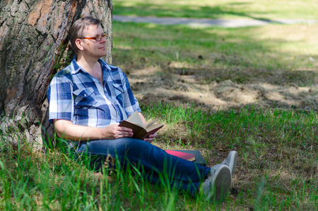 dreaminess: Man is reading book in pine forest near large trunk of old pine tree