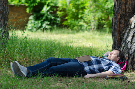 dreaminess: Man sleeps with open book on green lawn at old pine
