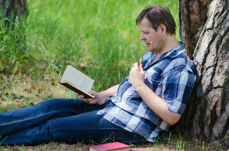 attentively: Sitting near trunk of old pine man reads book attentively Stock Photo
