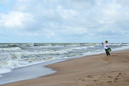 restless: KLAIPEDA, LITHUANIA - JULY 11, 2015: Elderly woman on shore of restless Baltic Sea photographs landscape