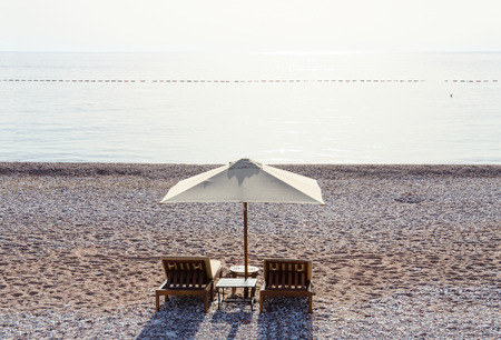 sultry: Sunbeds on sandy pebbled beach in sultry September day, Budva Riviera, Montenegro Stock Photo