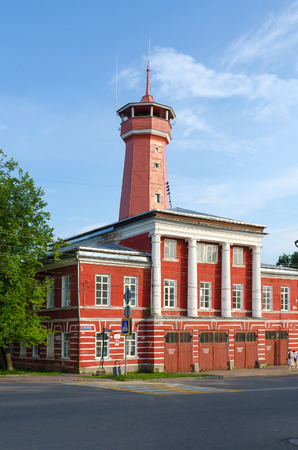 19 years: UGLICH, RUSSIA - JULY 19, 2016: Unknown people walk down street near building of fire department with watchtower. Building was built in years 1809-1811 on standard project. Project author Luigi Rusca