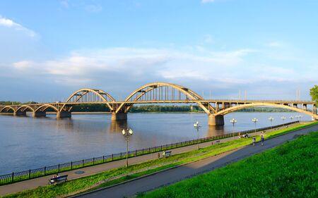 the volga river: RYBINSK, RUSSIA - JULY 21, 2016: Unidentified people walk along Volga embankment near automobile bridge over Volga River, Rybinsk, Russia