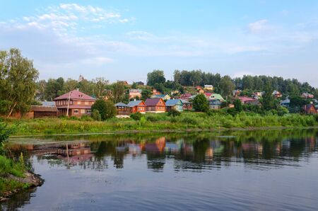 View of quiet provincial town of Ples on shore of pond in summer twilight, Russia