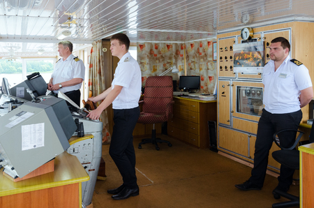 attentiveness: VOLGA RIVER, RUSSIA - JULY 19, 2016: Captain of river cruise ship Alexander Benois and mates of captain in captains cabin