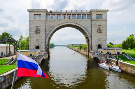 expects: UGLICH, RUSSIA - JULY 19, 2016: Russian flag on background of arch of navigation lock of  Uglich hydroelectric power station. Team of unknown yachtsmen expects decline of water level for passage of gateway