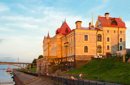 RYBINSK, RUSSIA - JULY 21, 2016: Unidentified people walk on promenade near old building of Rybinsk State Historical-Architectural and Art Museum-Reserve in sunset light, Russia