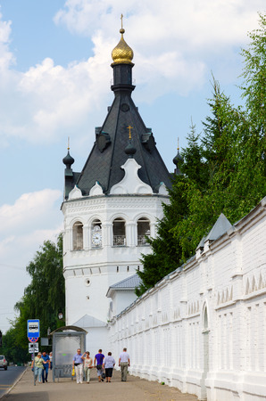 kostroma: KOSTROMA, RUSSIA - JULY 20, 2016: Unidentified people walk down street along wall of Theophany Convent (tower of XVII century, transformed in XIX century to monastery bell tower), Kostroma, Russia
