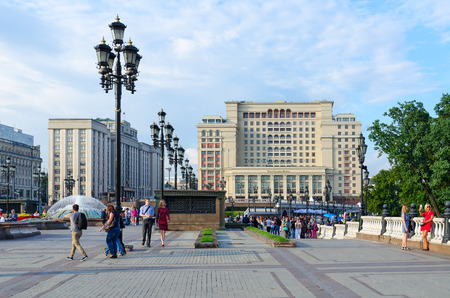 duma: MOSCOW, RUSSIA - JULY 23, 2016: Unidentified people walk on Manezhnaya Square near Four Seasons Hotel Moscow 5 * (previously -  hotel Moscow) and  building of State Duma of Russian Federation Editorial