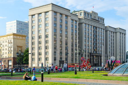 duma: MOSCOW, RUSSIA - JULY 23, 2016: Unidentified people walk on Manezhnaya Square and Street Okhotny Ryad near building of State Duma of Russian Federation, Moscow, Russia Editorial