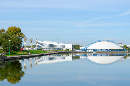 svisloch: MINSK, BELARUS - OCTOBER 1, 2016: View of Palace of Sports and indoor ice skating rink on waterfront of River Svisloch. Unidentified people are strolling along promenade on sunny autumn day Editorial