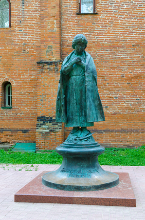 UGLICH, RUSSIA - JULY 19, 2016: Monument to Tsarevich Dimitry near brick walls of House of Uglich feudal princes in Uglich Kremlin, Russia