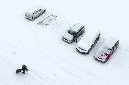 heavy snow: Cyclone Axel on territory of Belarus. Top view of cars in courtyard during heavy snowfall