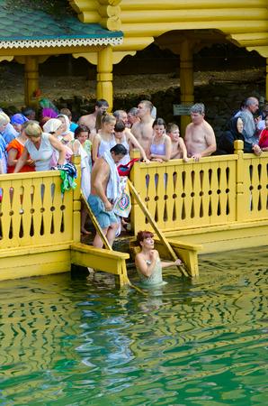pila bautismal: TSYGANOVKA, RUSIA - 22 DE AGOSTO DE 2015: Los peregrinos están en la fuente santa en el nombre de St. Serafín de Sarov cerca de la aldea de Tsyganovka, Rusia Editorial