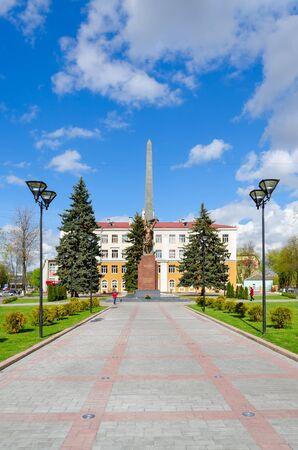 octahedral: GOMEL, BELARUS - APRIL 23, 2016: Unidentified people walk down street near monument to Komsomol-underground fighters at intersection of Streets Karpovicha and Zharkovskogo, Gomel, Belarus Editorial