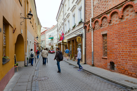 VILNIUS, LITHUANIA - JULY 10, 2015: Unknown people go along narrow Stikliu Street in Old Town, Vilnius, Lithuania