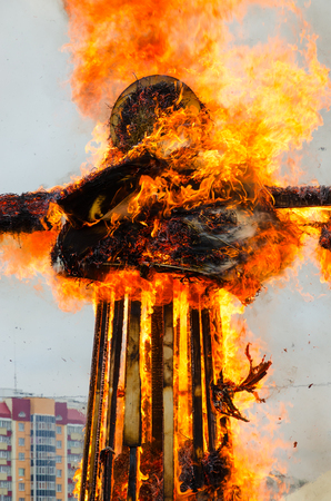 ablaze: Burning scarecrow of Shrovetide in bright flame on background of city building and sky