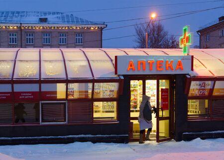 GOMEL, BELARUS - JANUARY 5, 2017: Unknown woman enters into pharmacy in winter evening, Sovetskaya Street, Gomel, Belarus Editorial
