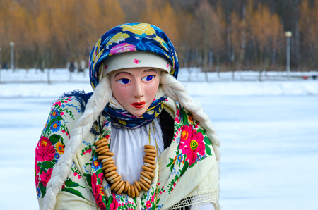 Shrovetide doll in colorful shawls, shirt and fur sleeveless jacket with bunch of bagels on neck Banque d'images