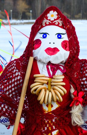 Shrovetide doll in red costume and knitted shawl with bunch of bagels on neck Stock Photo