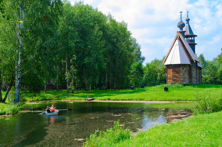 KOSTROMA, RUSSIA - JULY 20, 2016: Kostroma Architectural-Ethnographic and Landscape Museum-Reserve Kostromskaya Sloboda. Church of All-Merciful Savior on bank of river Igumenka. Unknown people ride boat