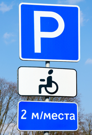 Informational and indicative traffic sign Place of parking and sign of additional information (plaque) Invalids against sky