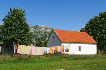 balkans: Village of Negushi in mountainous area, Montenegro. Bed linen and clothes is dried on ropes near one-storey village house Stock Photo
