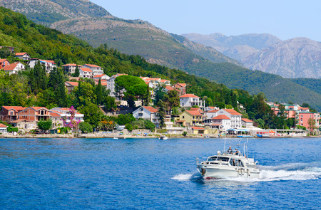 16: KOTOR BAY, MONTENEGRO - SEPTEMBER 16, 2015: Beautiful view from sea on coast and resort village at foot of mountains, Kotor Bay, Montenegro. Unidentified people sail on boat Editorial