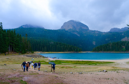ZABLJAK, MONTENEGRO - SEPTEMBER 12, 2017: Unknown tourists are on shore of Black Lake in National Park Durmitor on rainy September day, Montenegro Editorial
