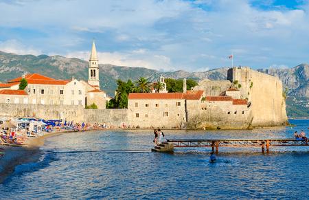 BUDVA, MONTENEGRO - SEPTEMBER 5, 2017: Unknown people rest on beach near Old Town in popular resort of Budva, Montenegro