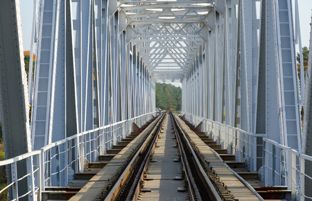 Structure of old railway bridge across river. Rails of railroad tracks, stretching into perspective Stock Photo