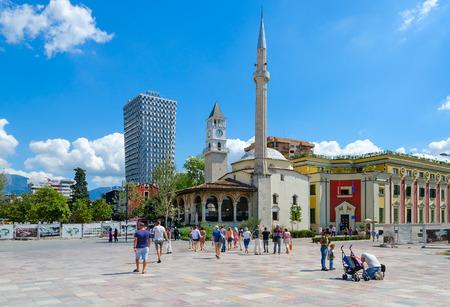 TIRANA, ALBANIË - SEPTEMBER 6, 2017: Groep onbekende toeristen op Skanderbeg-Vierkant. Efem Bay-moskee, klokkentoren, Plaza Hotel, Tirana, Albanië