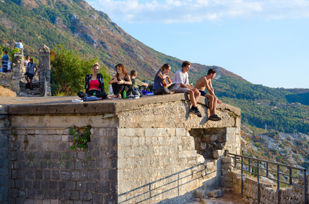 KOTOR, MONTENEGRO - SEPTEMBER 8, 2017: Unknown tourists are on ruins of fortress of St. John (Illyrian Fort) over city of Kotor, Montenegro Editorial