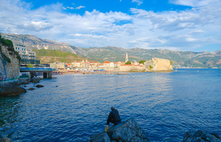 Fisherman sits on rocks against background of sea and Old Town of Budva, Montenegro