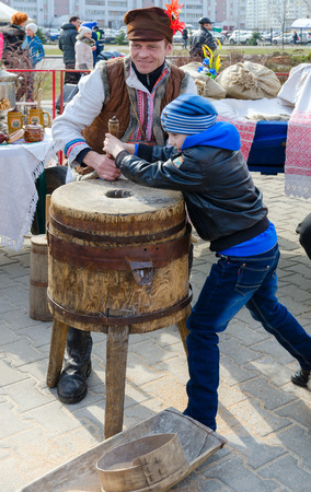 GOMEL, BELARUS - MARCH 12, 2016: Unknown man demonstrates work of old hand-made mill to boy during Shrovetide entertainment program on open air 에디토리얼