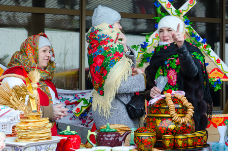 GOMEL, BELARUS - FEBRUARY 18, 2018: Three women are at table with pancakes, small bagels and painted utensils during Shrovetide festivities
