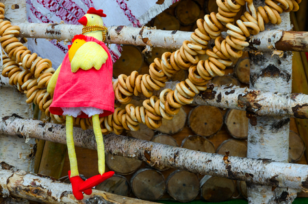 GOMEL, BELARUS - FEBRUARY 18, 2018: Shrovetide festivities. Decor of trade places. Toy-rooster and bundle of bagels, hanging on birch fence against background of woodpile Editorial