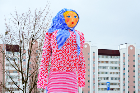 Scarecrow of Shrovetide in multicolored outfit against sky and city building, Gomel, Belarus Stock Photo