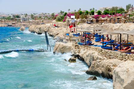 SHARM EL SHEIKH, EGYPT - MAY 8, 2018: Unknown people rest on beach of hotel Siva Sharm (ex. Savita Resort) 5 * in Sharks Bay. Warning red flag on beach Editorial