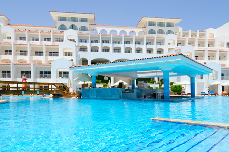 SHARM EL SHEIKH, EGYPT - MAY 8, 2018: Unknown people are resting on territory of hotel Siva Sharm (ex Savita Resort) 5 * in Sharks Bay. Main building and pool bar