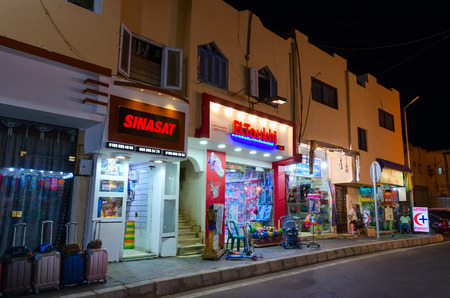 SHARM EL SHEIKH, EGYPT - MAY 15, 2018: Unknown sellers are on street at entrance to shops in Old Market. Residential upper floors in houses, evening view Éditoriale