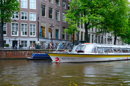 AMSTERDAM, NETHERLANDS - SEPTEMBER 6, 2018: Unidentified tourists are on sightseeing pleasure boat on canal in historic center of city, Amsterdam, North Holland, Netherlands