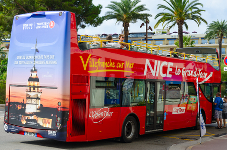 NICE, FRANCE - SEPTEMBER 15, 2018: Unidentified tourists sit in red double-decker sightseeing bus (Nice Le Grand Tour) in city center, Nice, France