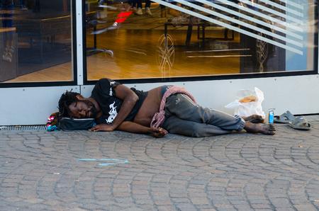PARIS, FRANCE - SEPTEMBER 7, 2018: Unknown homeless dark-skinned man is sleeping on street of Paris, France Editorial
