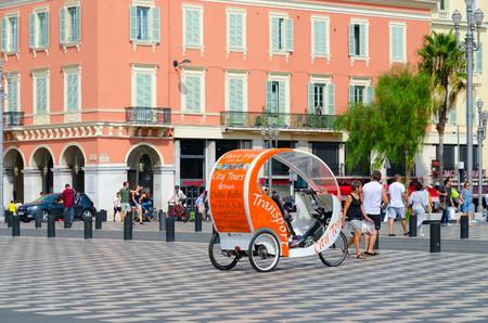 NICE, FRANCE - SEPTEMBER 15, 2018: Walking excursion bike car on Place Massena. Promenade du Paillon. Unknown people walk down street Redactioneel