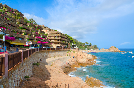 TOSSA DE MAR, SPAIN - SEPTEMBER 12, 2018: Beautiful view of embankment in popular resort town of Tossa de Mar, Costa Brava, Spain. Unknown people walking down street