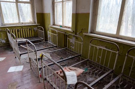 KOPACHI, UKRAINE - NOVEMBER 11, 2018: Bedroom in abandoned kindergarten in destroyed village of Kopachi (10 km exclusion zone of Chernobyl Nuclear Power Plant), Ukraine