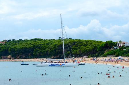 LLORET DE MAR, SPAIN - SEPTEMBER 9, 2018: Unidentified people relax on Fenals Beach in popular resort town of Lloret de Mar, Costa Brava, Catalonia, Spain
